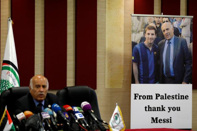 Poster of Palestinian FA chief Jibril Rajoub with Argentina's soccer player Lionel Messi is seen during Rajoub's news conference, in Ramallah in the occupied West Bank