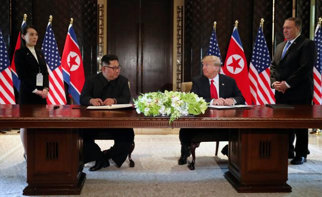 U.S. President Donald Trump and North Korea's leader Kim Jong Un look at each others before signing documents, at their summit in Singapore