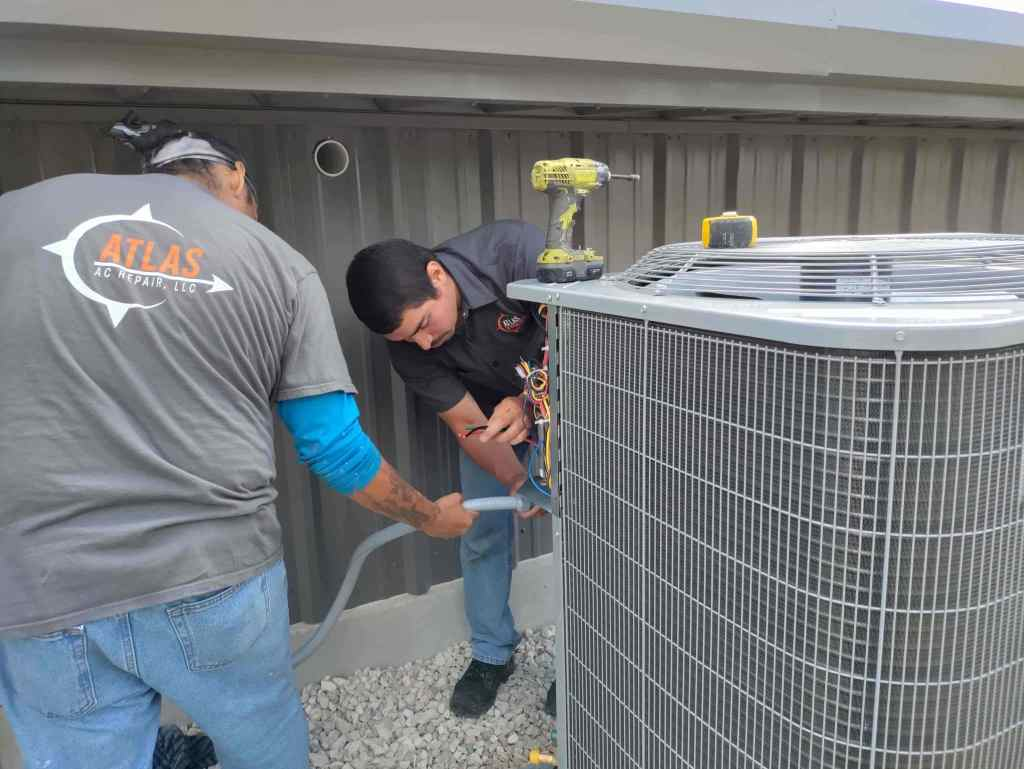 two technicians installing new ac condenser outside