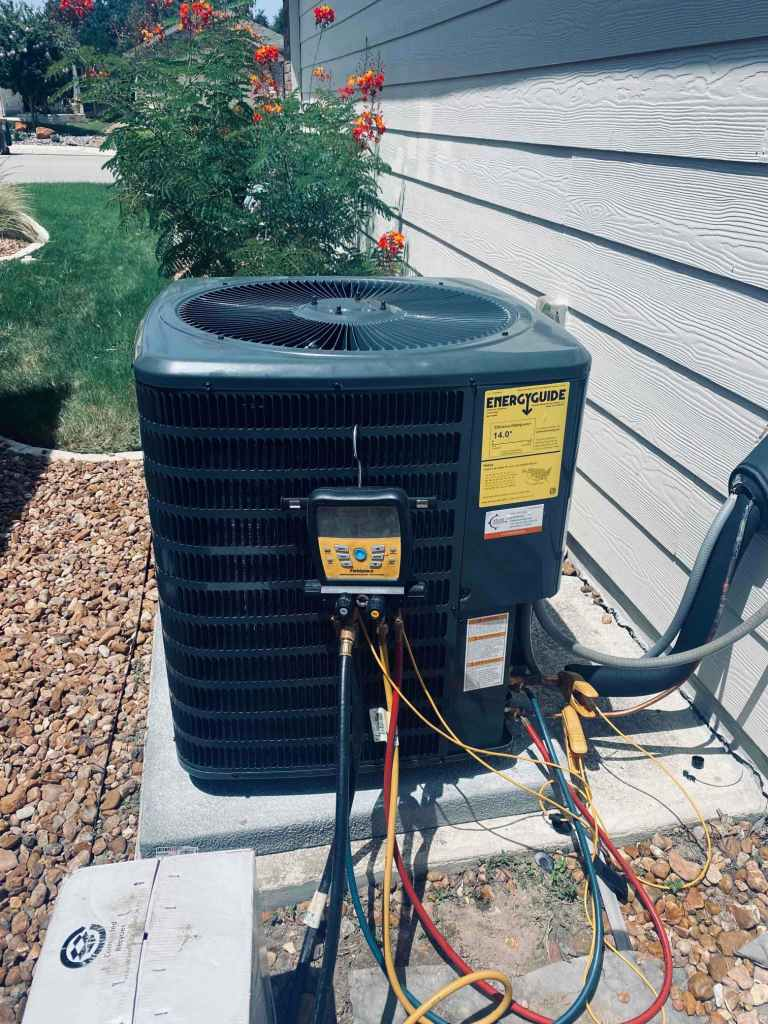 AC condenser connected to diagnostic tool used to inspect air conditioning units