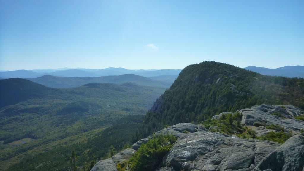A view shows a distant mountain range and a nearby rocky mountain covered in green trees.