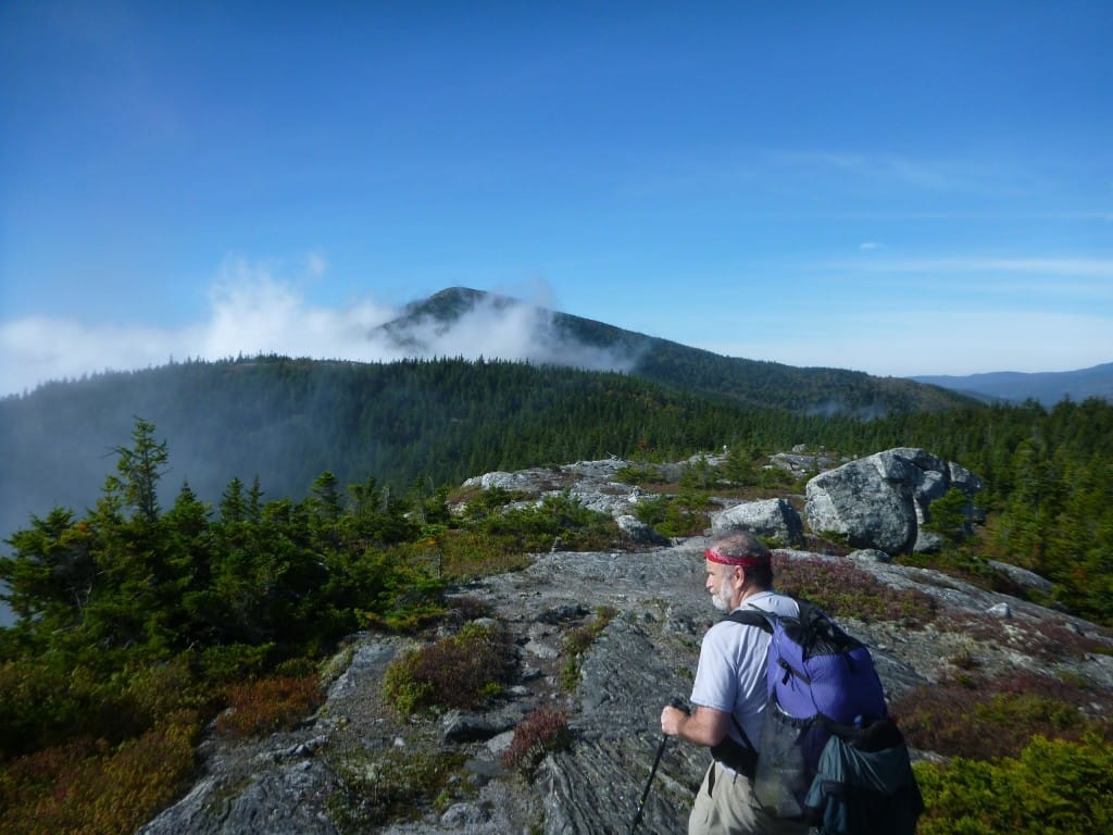 A hiker traverses a rocky mountain range in the White Mountains National Forest.