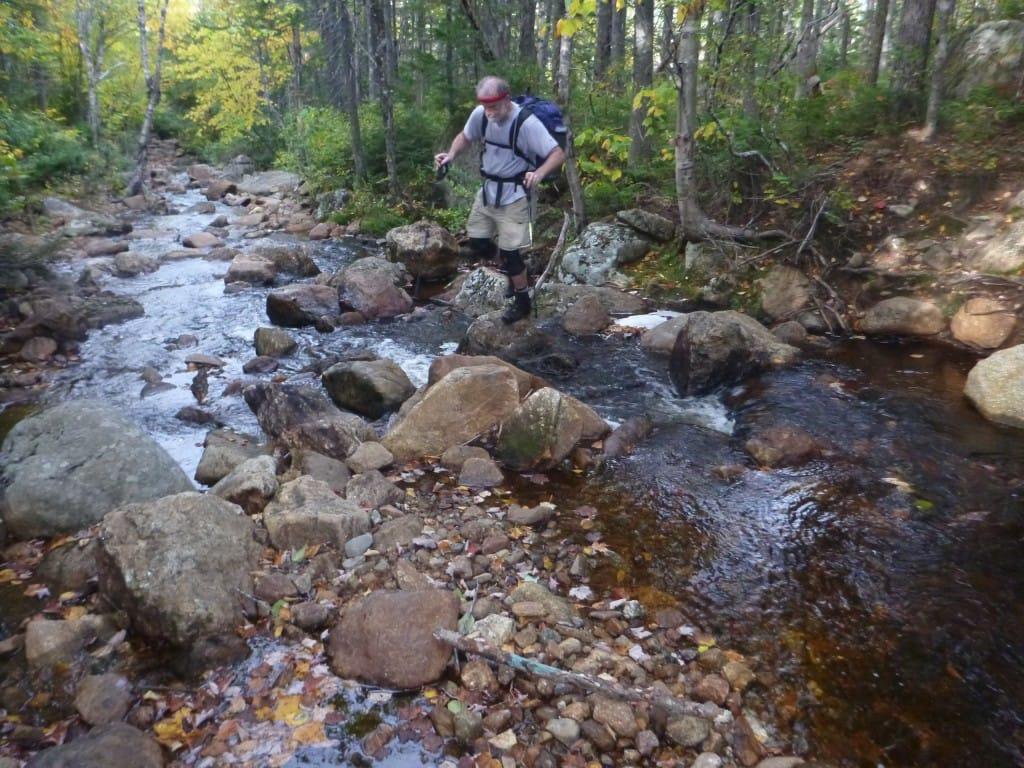 A hiker crosses a rocky stream.