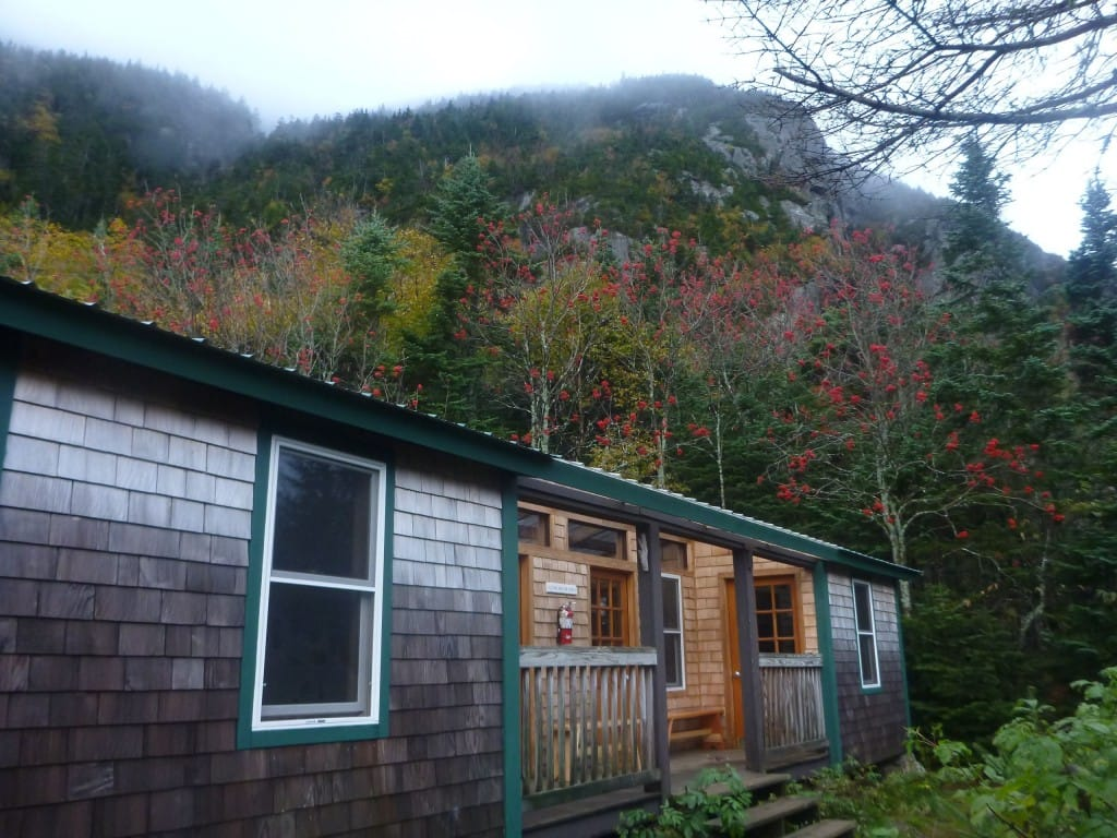 A building with wooden shingles sits nestled in a foggy green forest.
