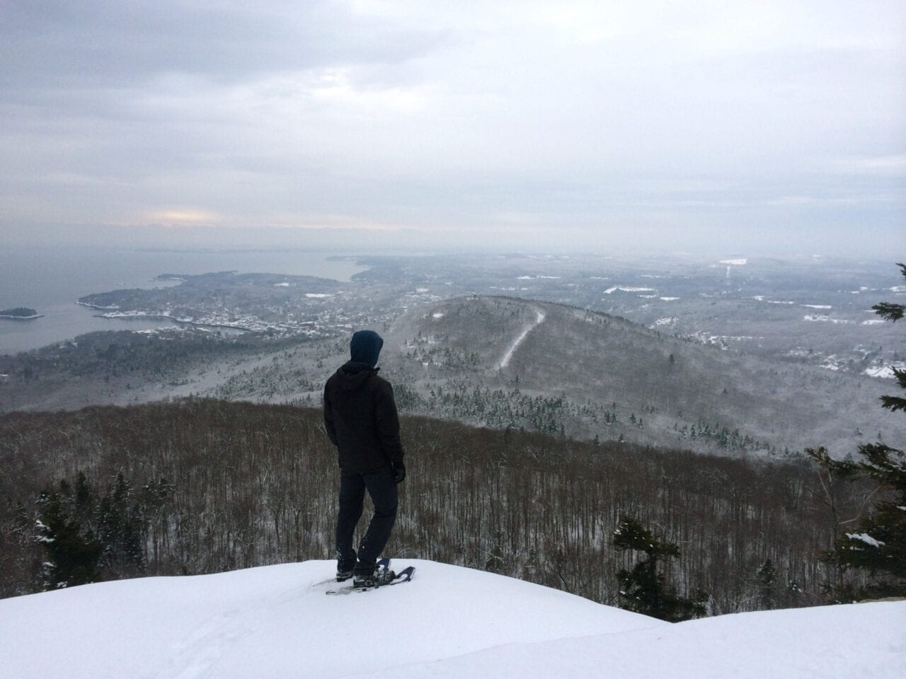 A hiker wearing snowshoes and standing on a snowy ridge looks out onto a foggy valley.