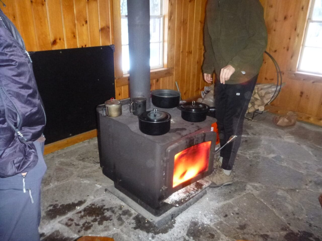A couple people warm themselves next to a woodstove.