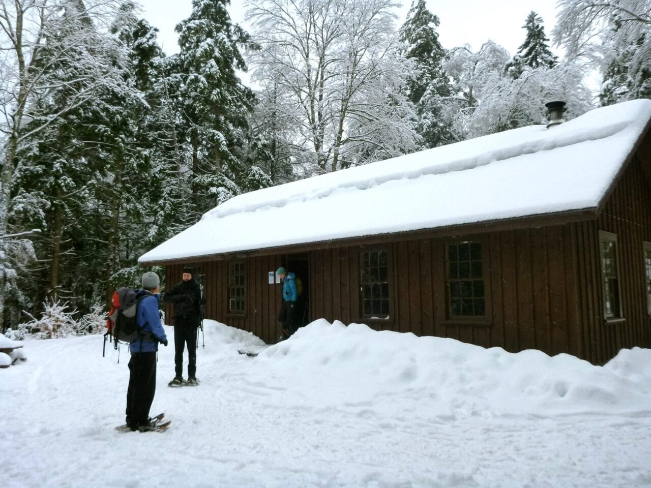 A few hikers stand in front of a snowy cabin.