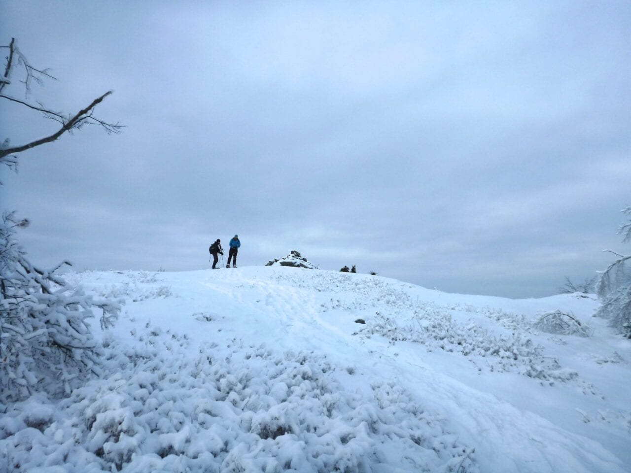 A few hikers stand on a snowy hill in a meadow.