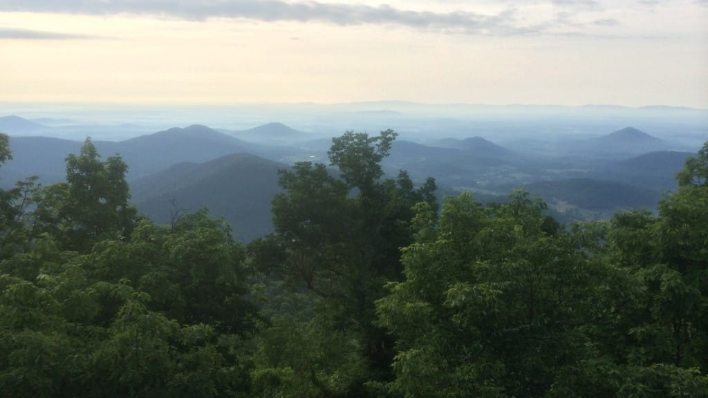 An early sunset illuminates trees and distant mountains from this overlook.