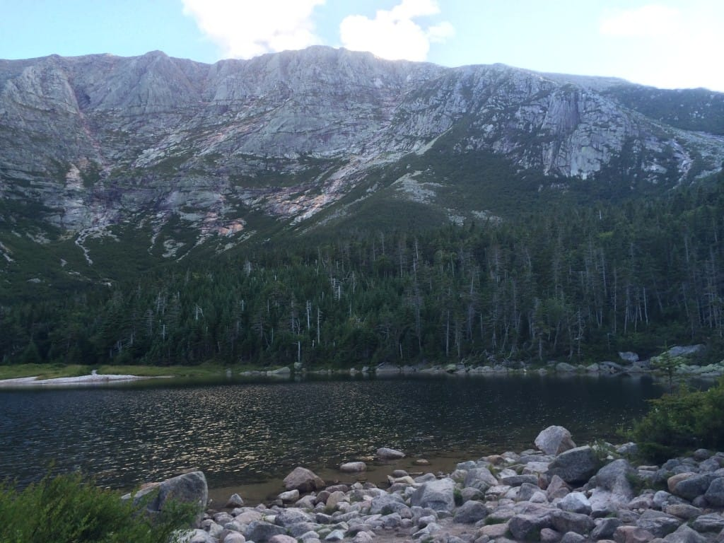 A lake is overshadowed by a large, rocky mountain.