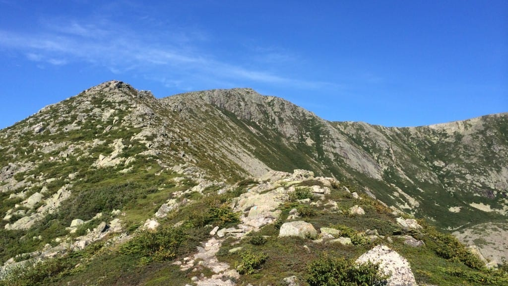 A rocky ridgeline sits under bright blue skies.