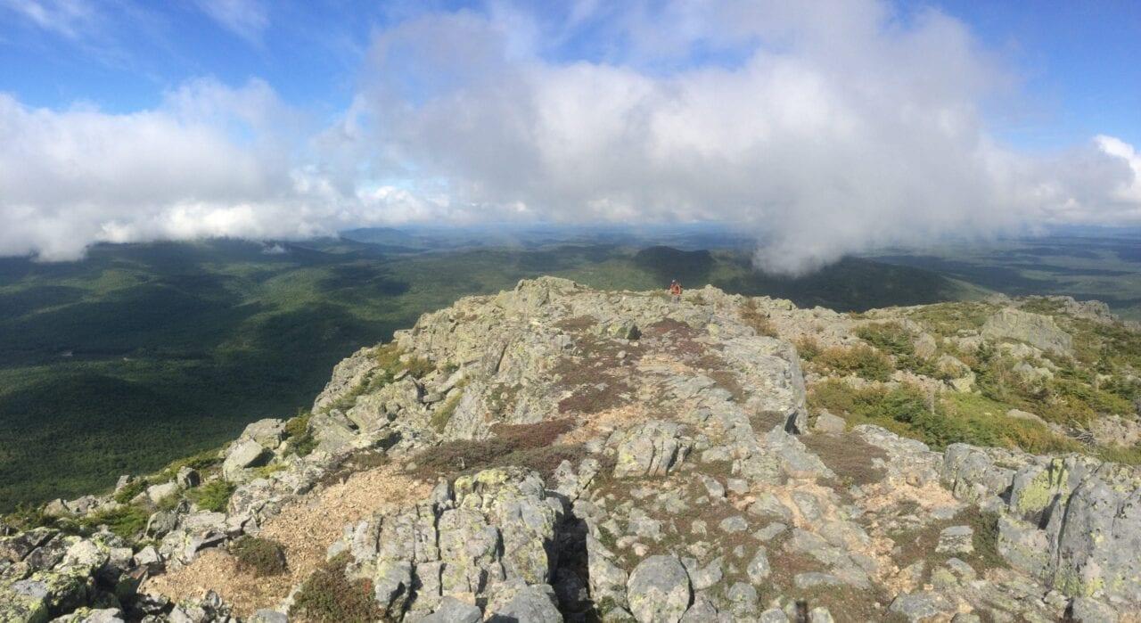 A distant hiker climbs a rocky ridge.