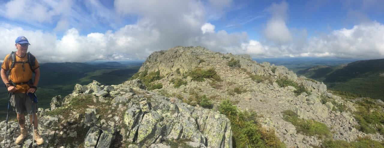A hiker stands on a rocky summit.