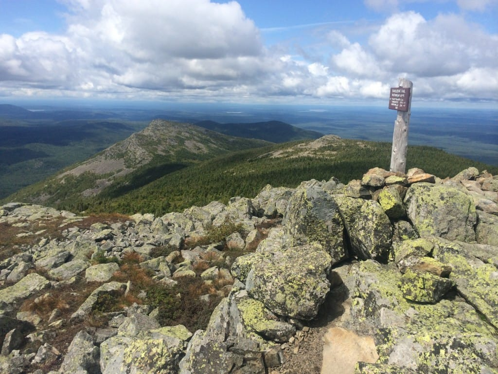A signpost points the way down a rocky ridge.