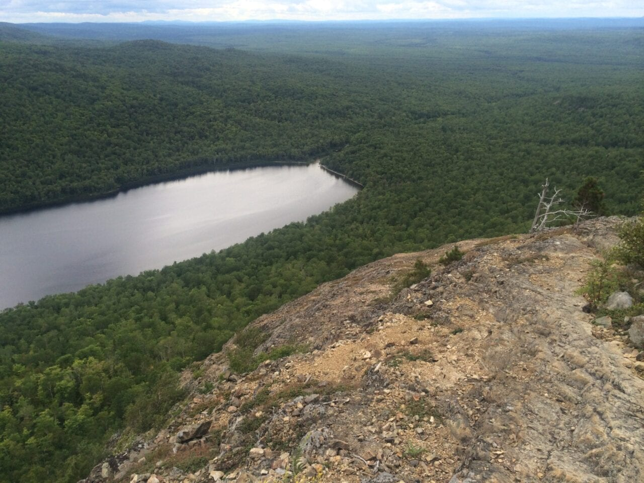 A rocky ridge offers views of a distant lake.