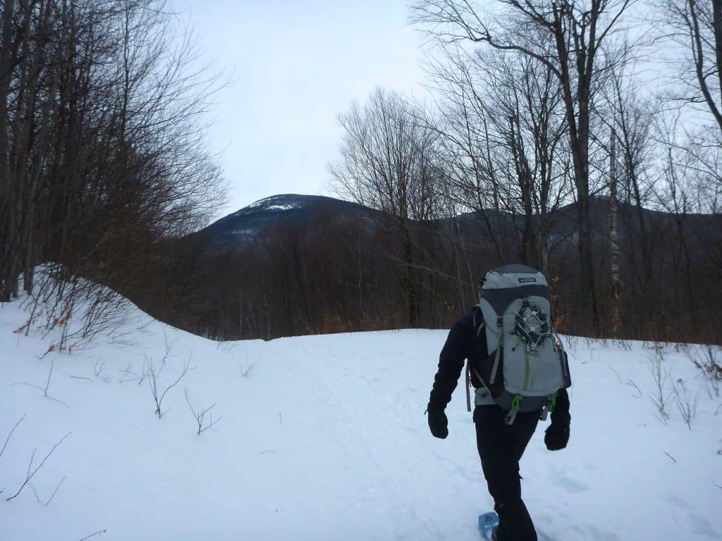 A lone hiker walks down a snowy trail towards a distant mountain range.