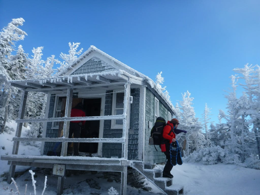 A hiker leaves a frost-covered cabin in a snowy forest.