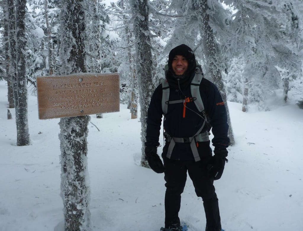 A hiker stands next to a trail sign in a snowy forest.
