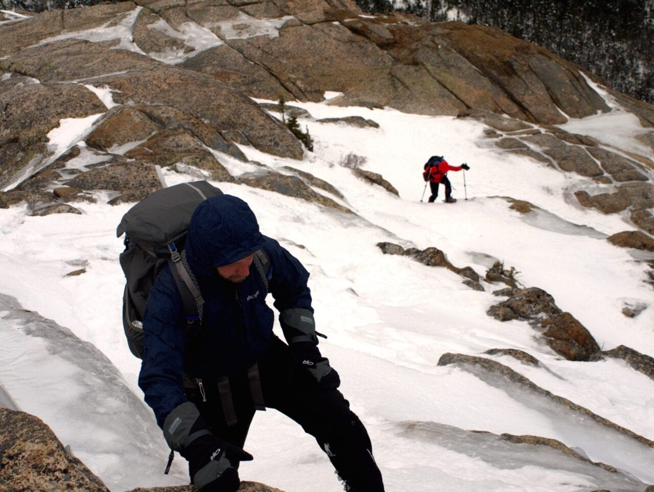Two hikers climb through a snow field.