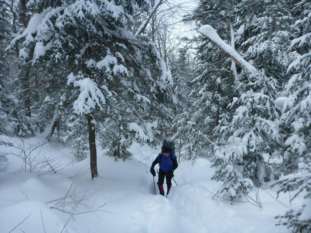 A hiker climbs a slope through deep snow.
