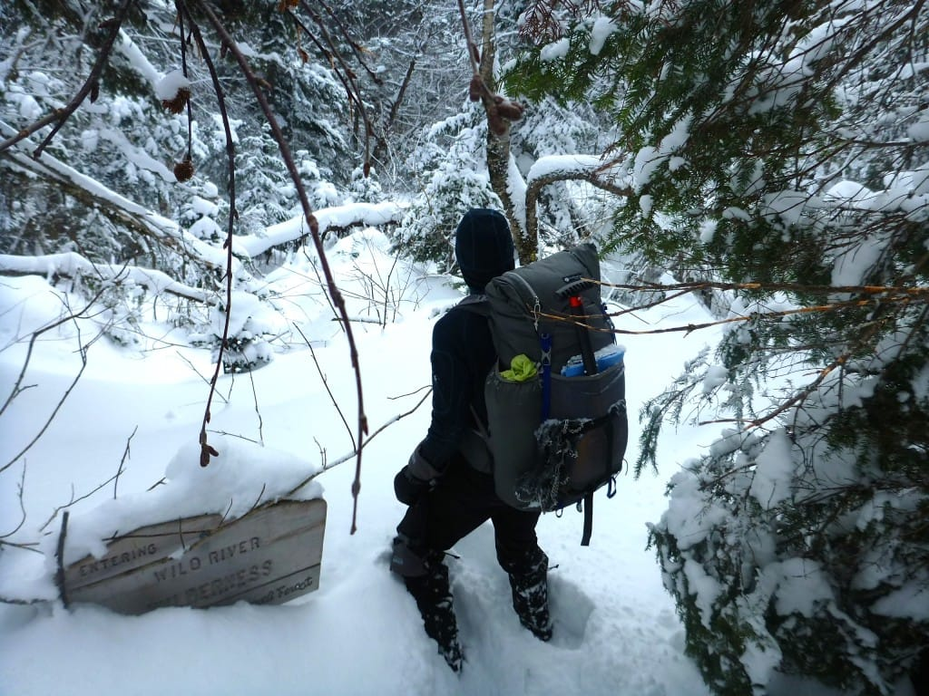 A hiker wades through deep snow.