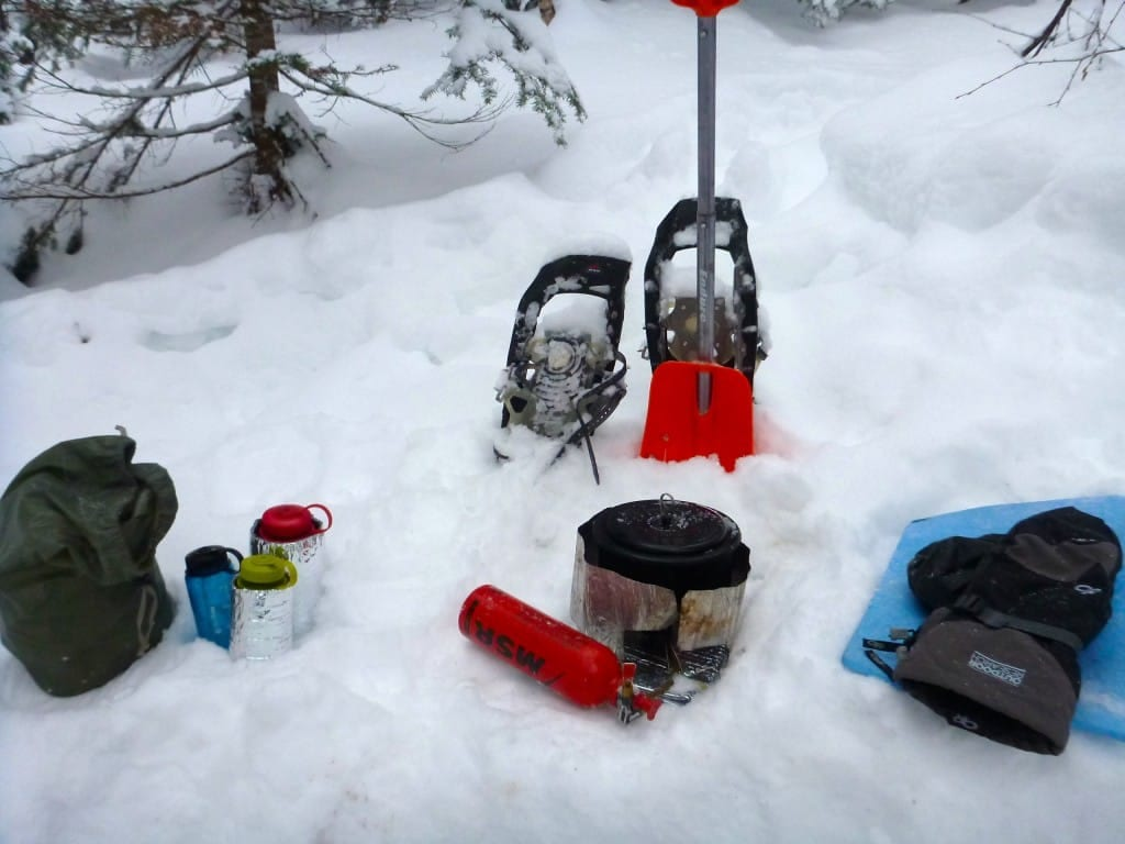 Hiking gear sits on the snowy ground.