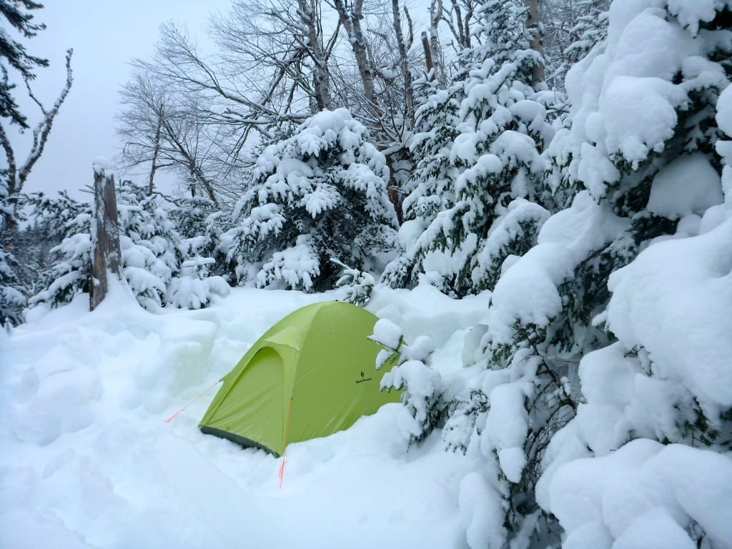A green tent sits in the deep snow, surrounded by snowy trees.