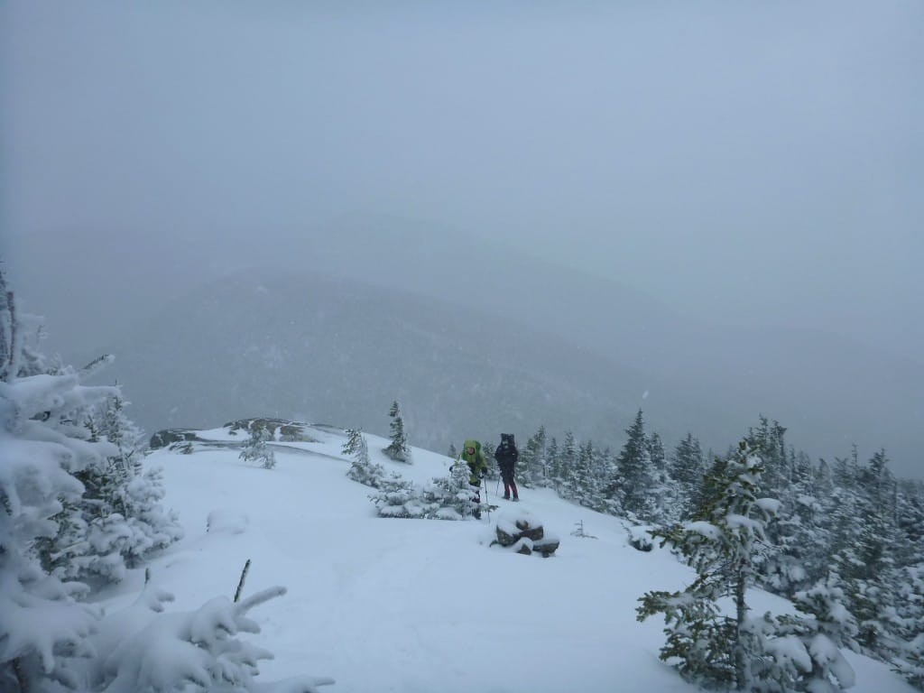 Two hikers stand on a snowy ridge, surrounded by fog.