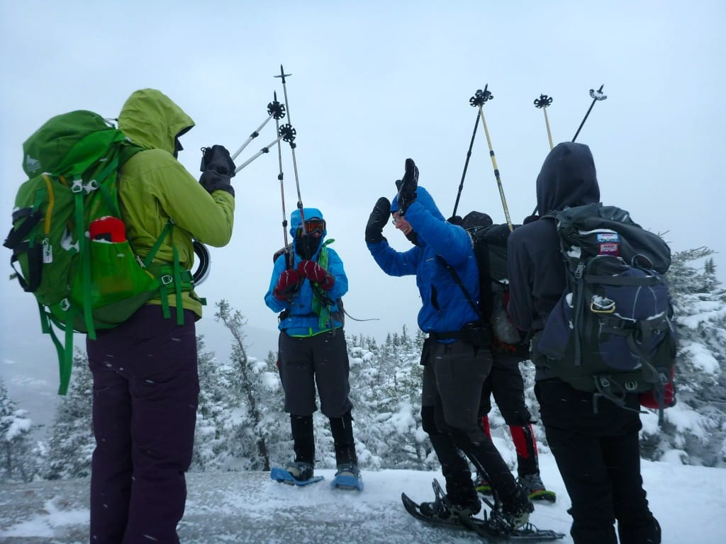 A group of hikers stand on a snowy summit and celebrate.