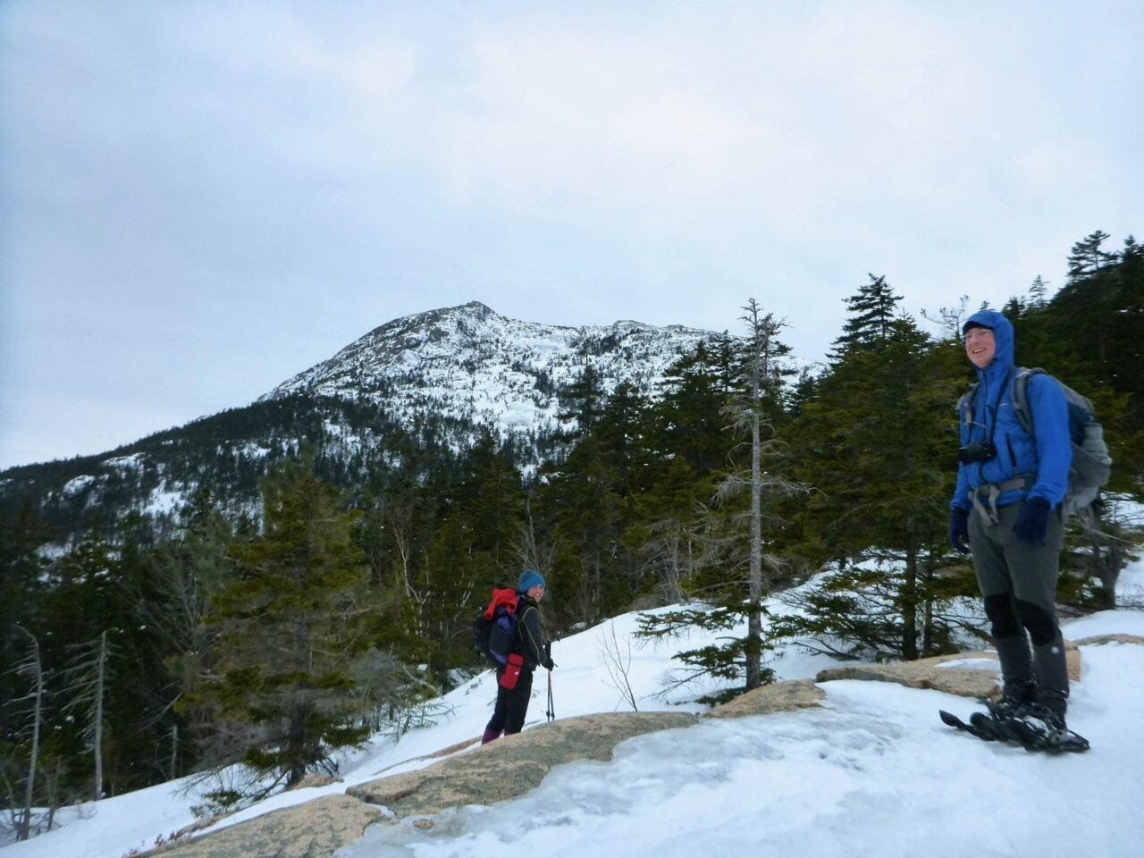 Two hikers stand in front of a view of a snowy mountain and evergreen forest.