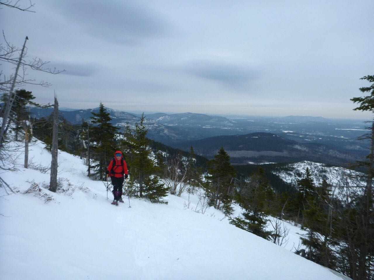 A hiker climbs up a snowy slope with a valley visible in the background.