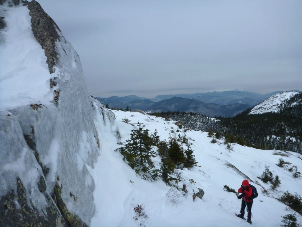 A hiker on snowy ground stands next to an imposing cliff.