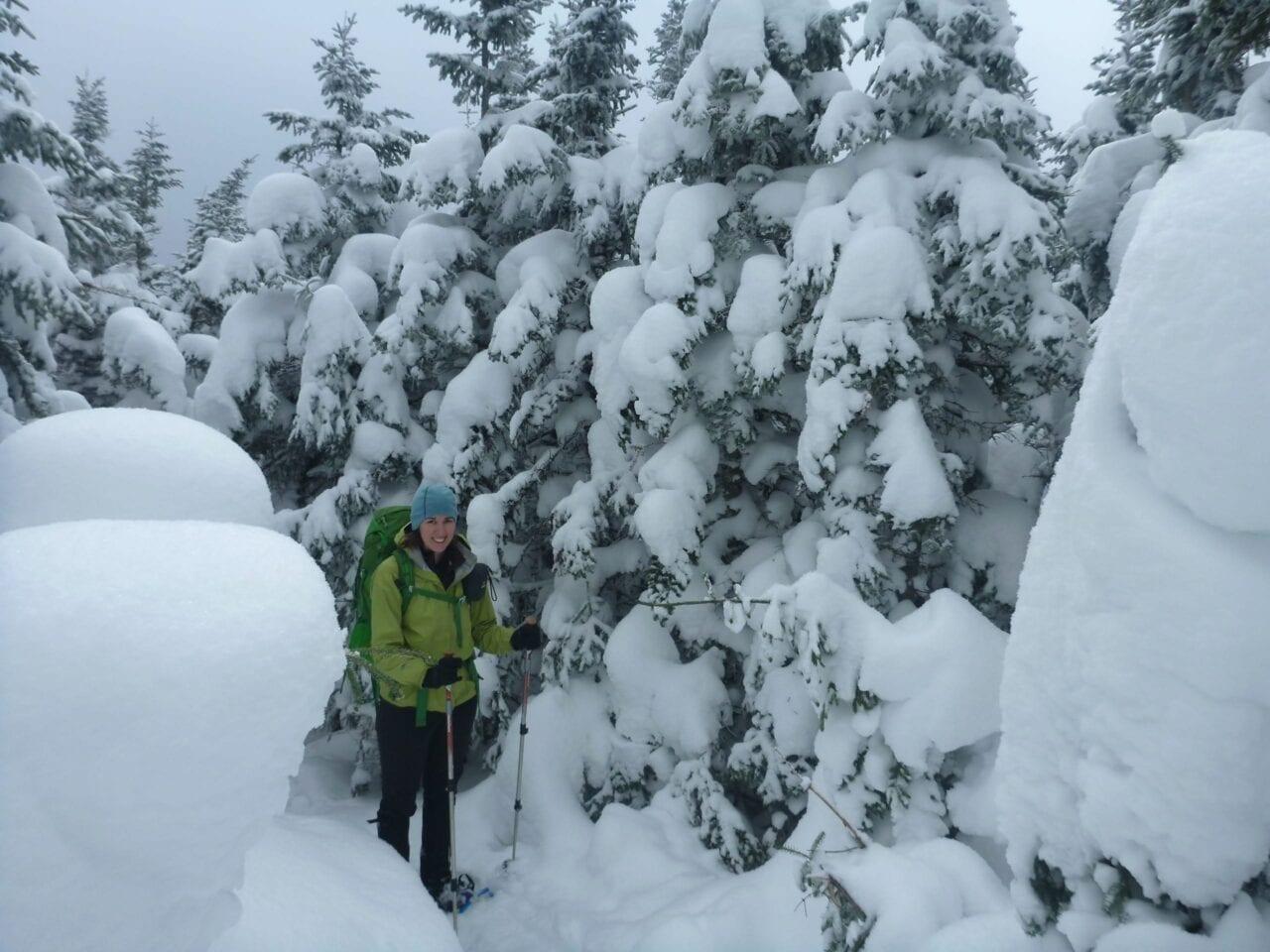A hiker walks down a snow-covered trail.