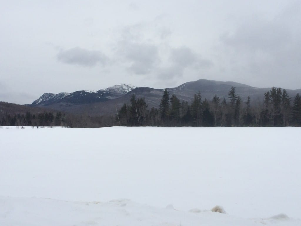 A snowy field sits in front of a gray sky and dark mountains.