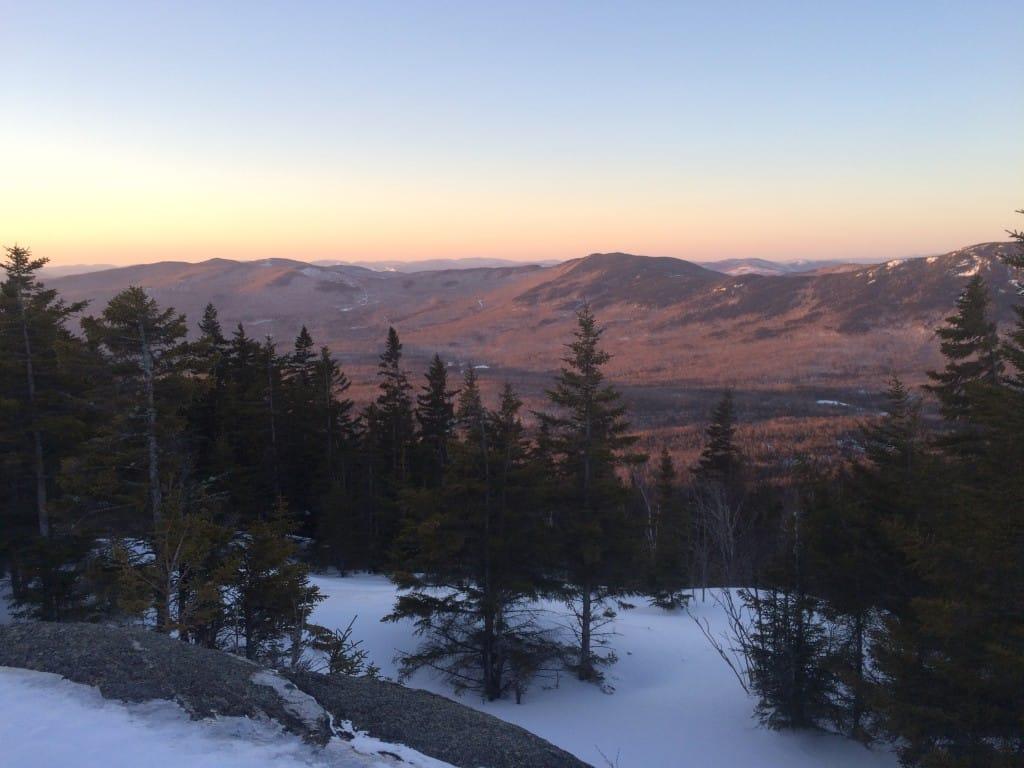 Sunlight illuminates the valley below a snowy ridge.