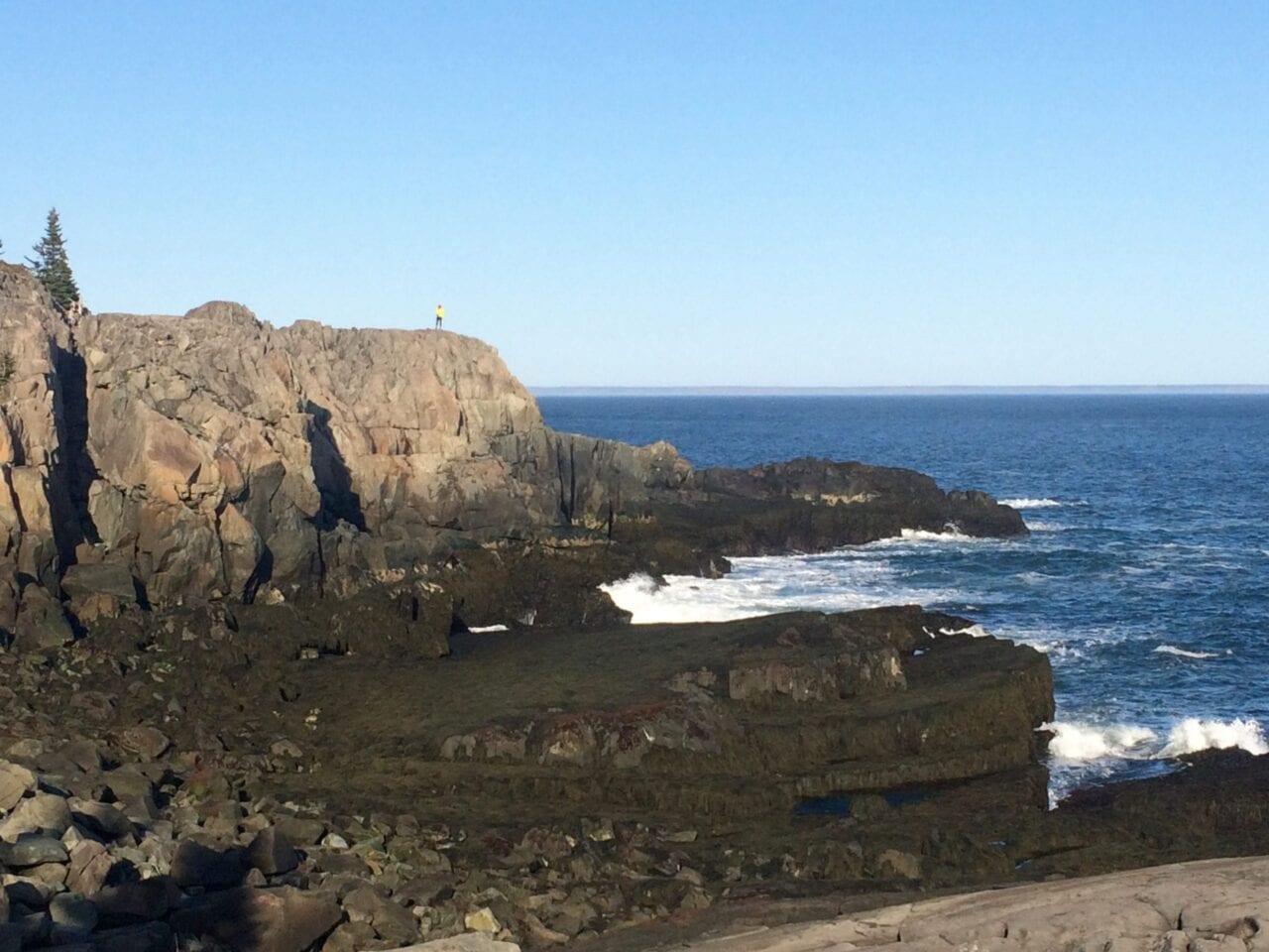 Blue skies and water meet a rocky coastline.