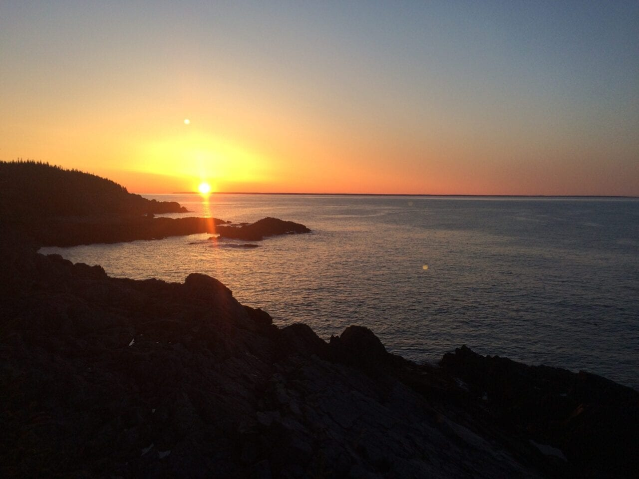 A sunrise glows over a rocky coastline and calm ocean waters.