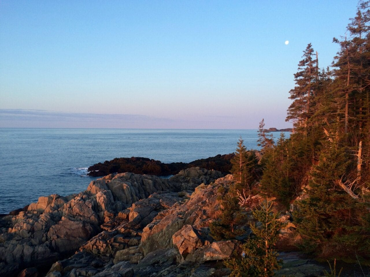 A pink sunrise appears over a rocky coastline and blue ocean waters.
