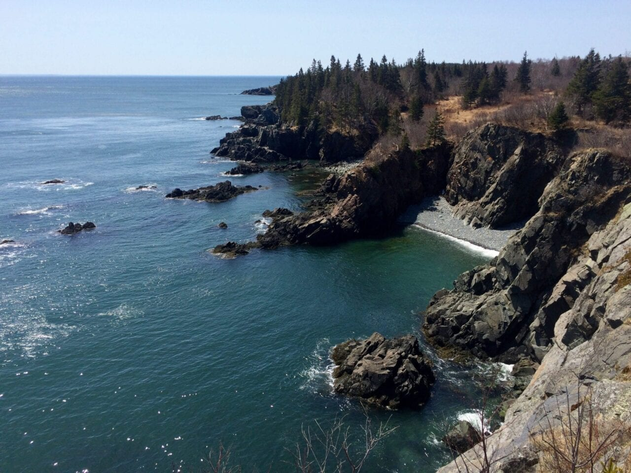 Teal ocean water meets prominent rocky cliffs on Maine's coastline.