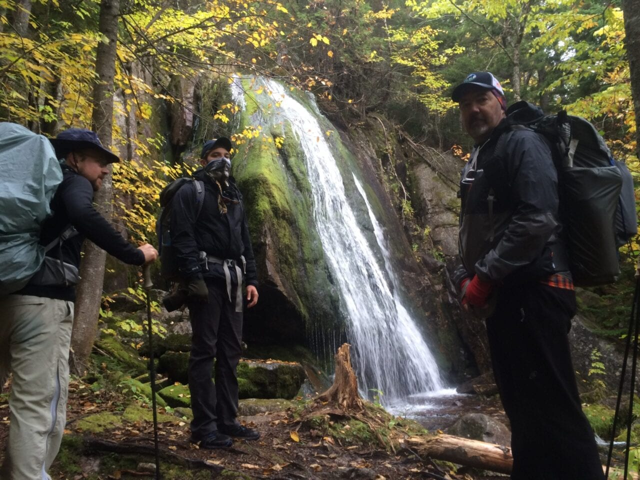 Three hikers stand in front of an exquisite waterfall in a forest.
