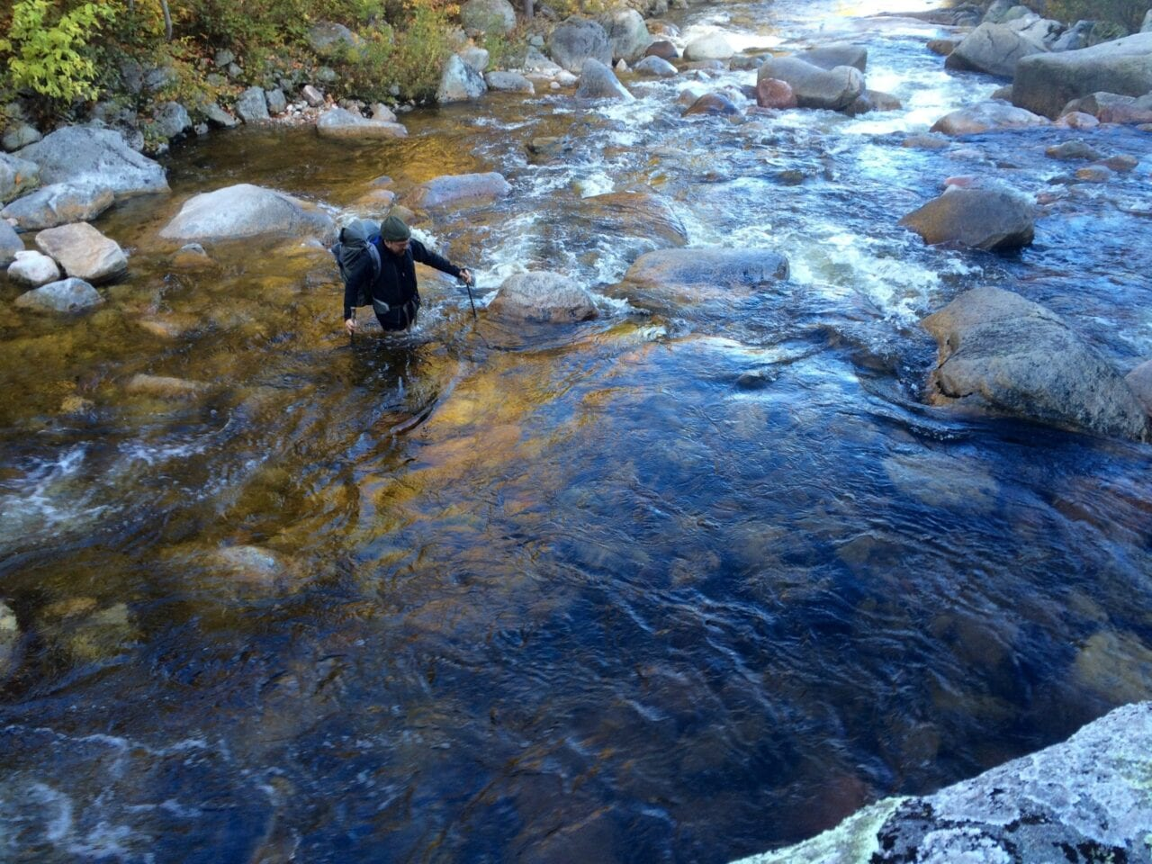 A hiker wades across a clear, flowing mountain river.