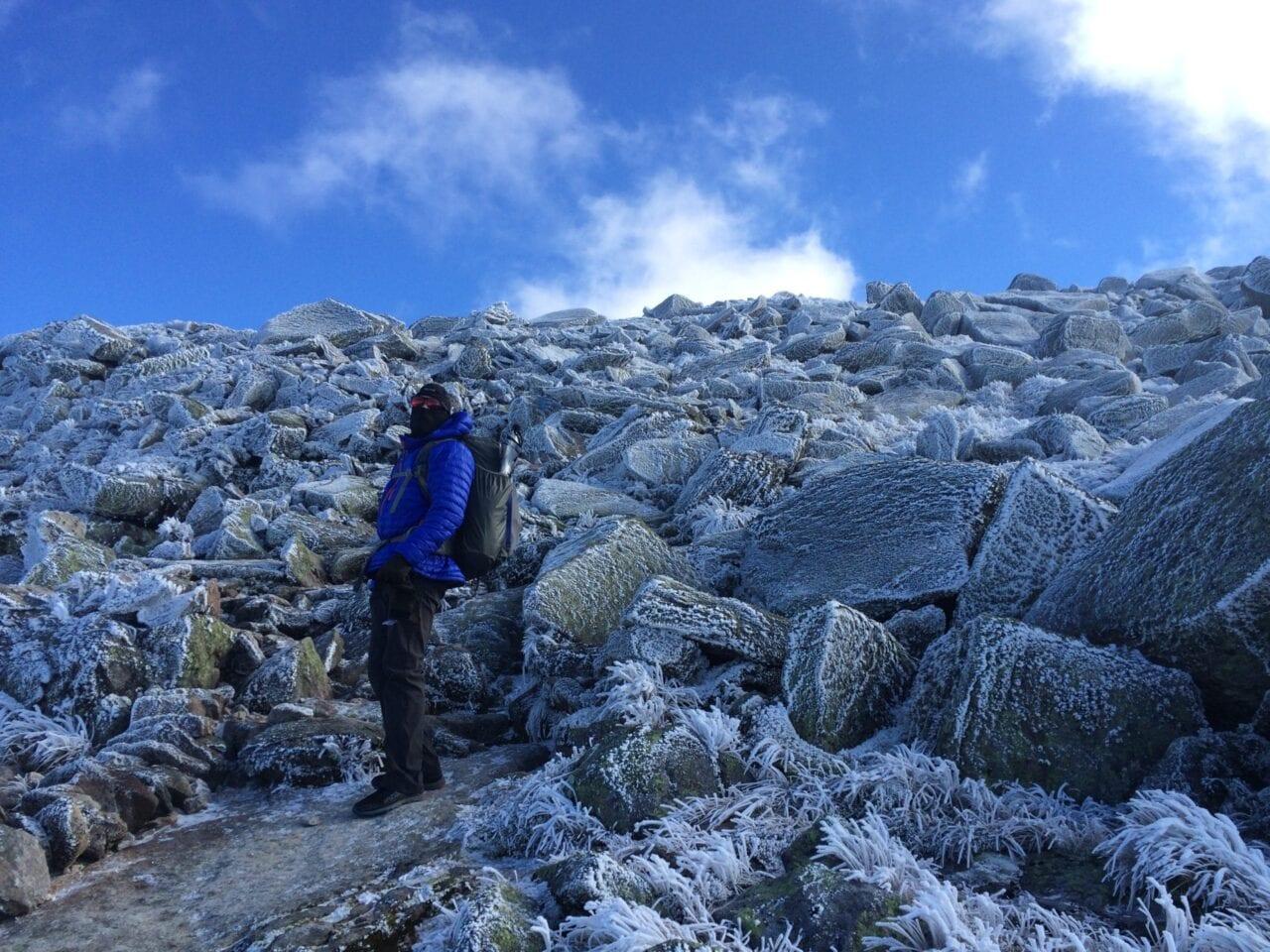 A hiker crosses a massive boulder field.