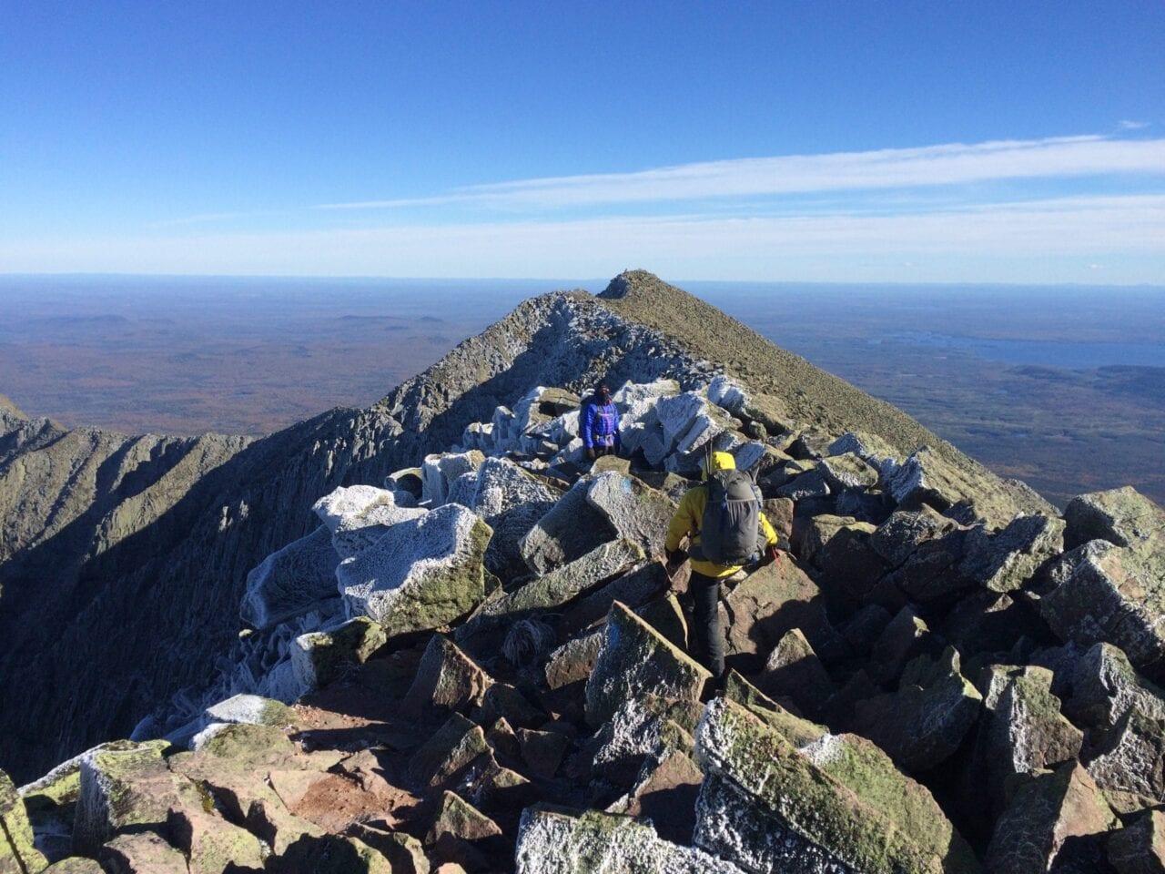 A rocky ridgeline overlooks a distant valley.