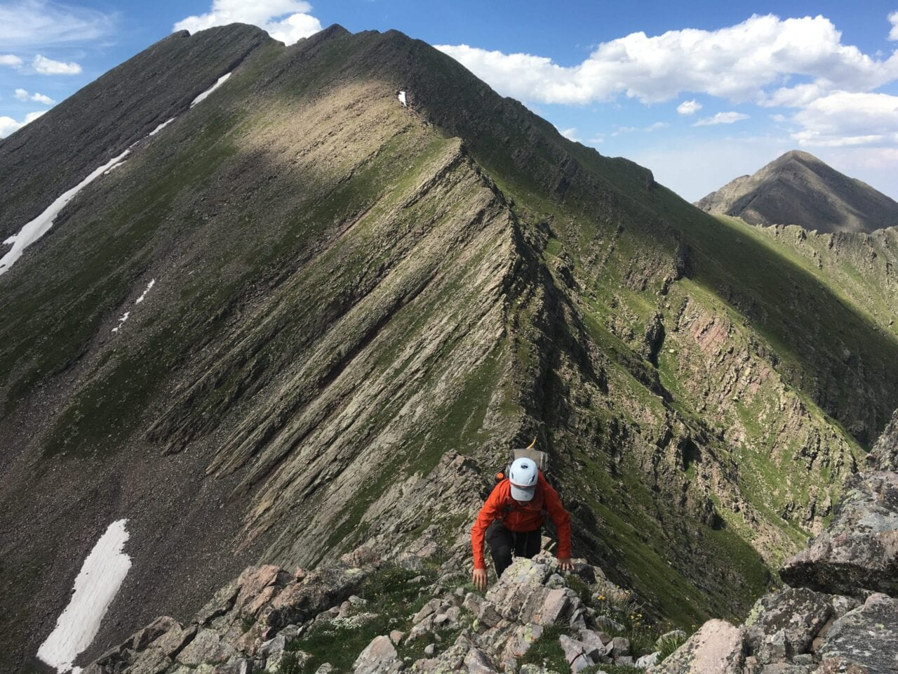 A hiker climbs a sharp rocky ridge with towering peaks behind them.