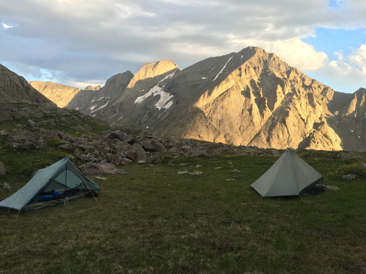 Two tents sit in a small field in front of towering ridgelines.
