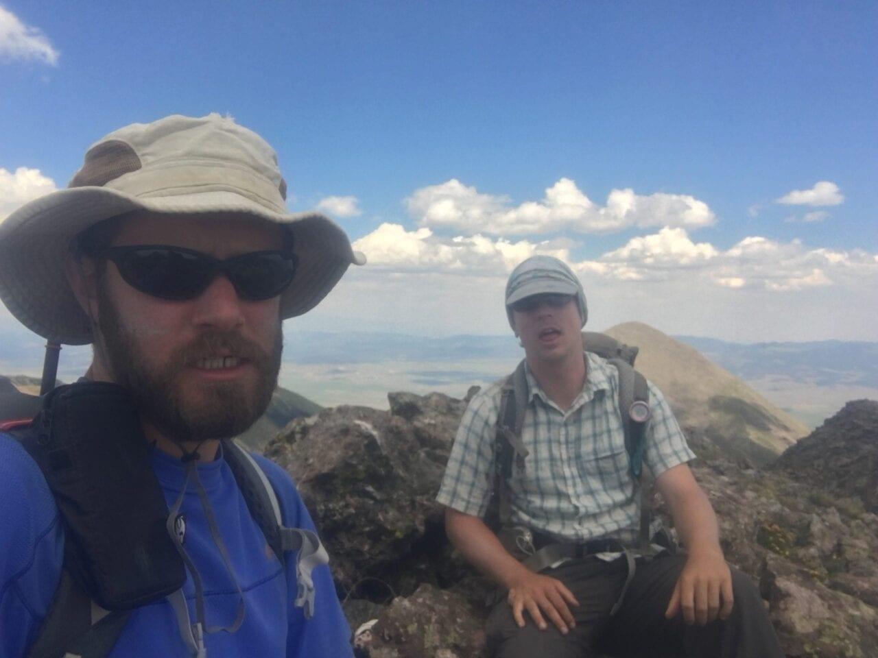 Two hikers sit on rocks on top of a rocky ridgeline.