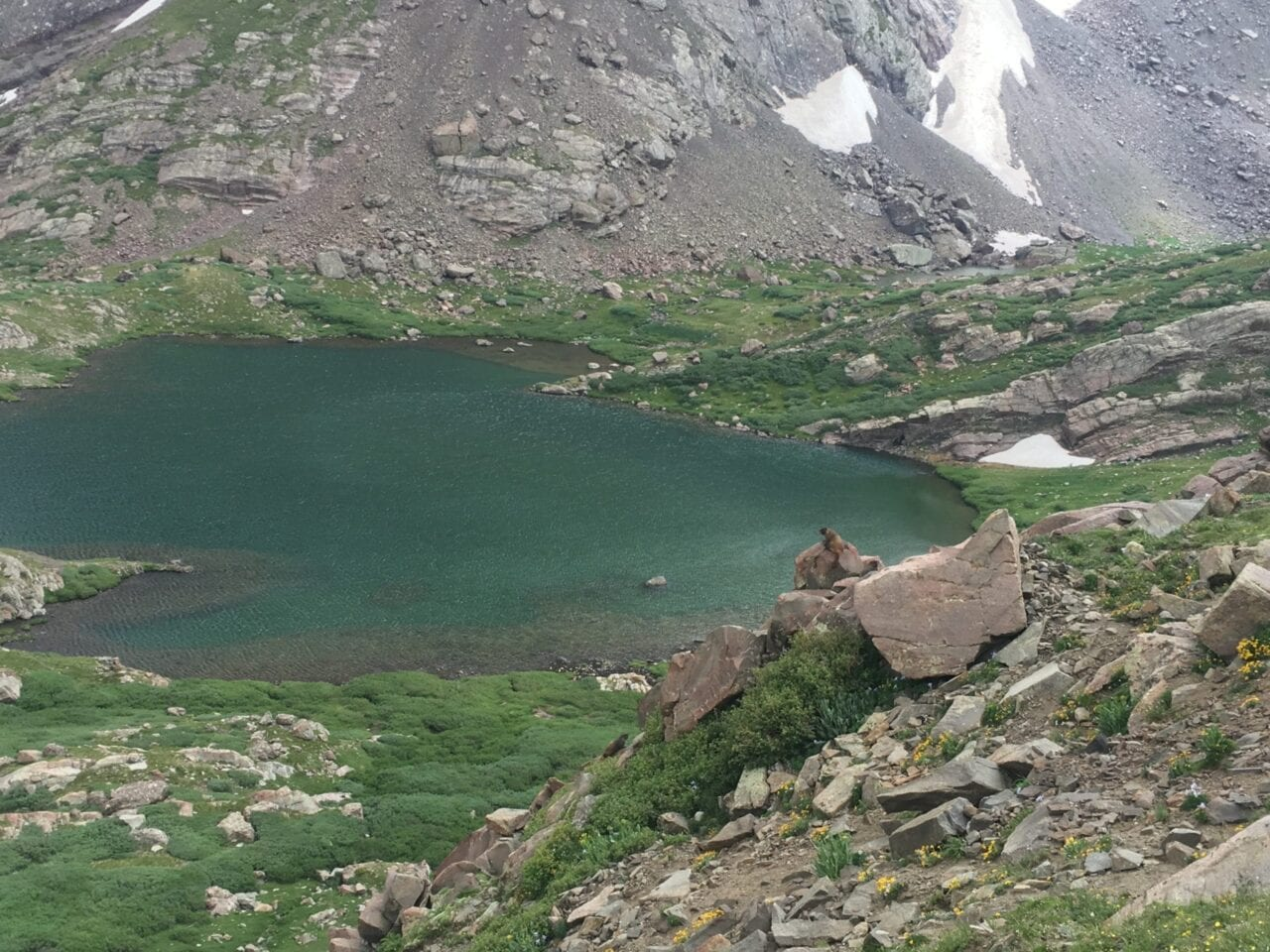 A view from a ridge showcases a blue lake surrounded by grass and rocks.