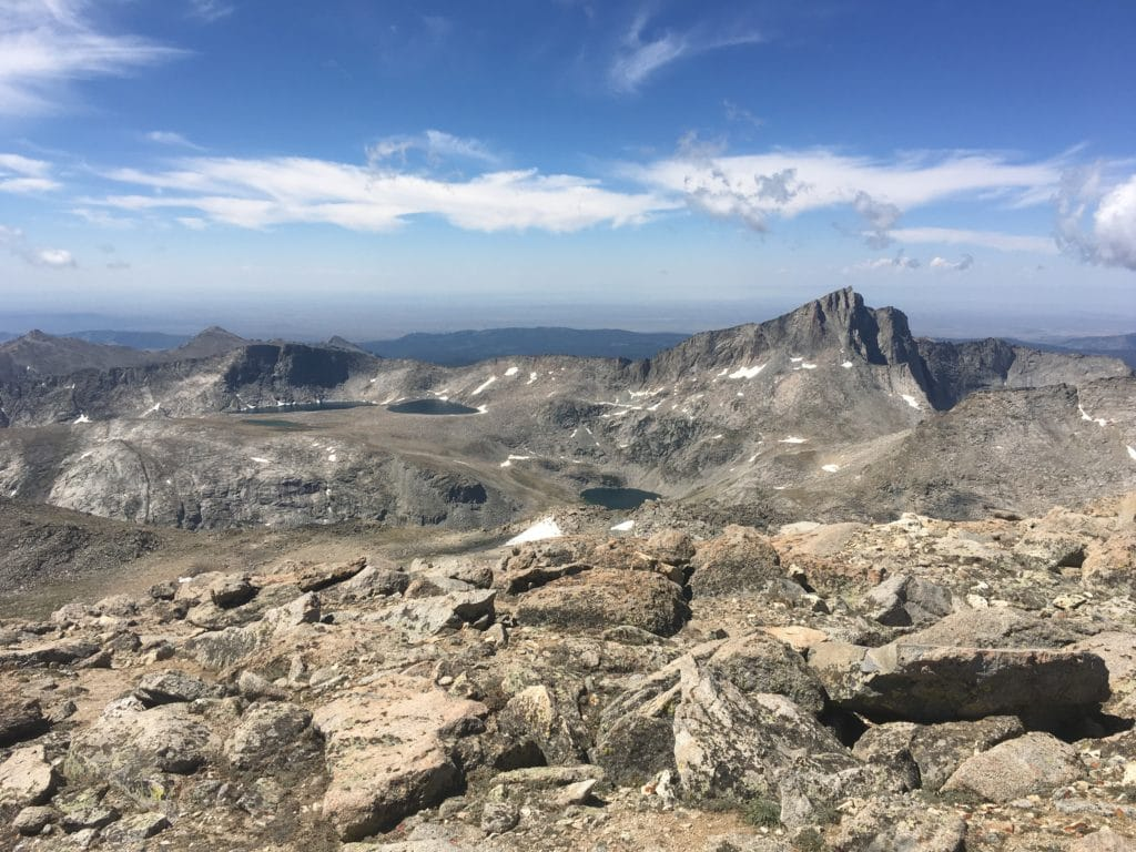 Blue skies and rocks showcase a mountainous ridgeline.