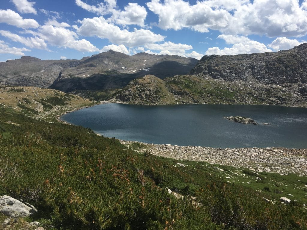 A view from a ridgeline shows a blue lake nestled in imposing rocky ridgelines.