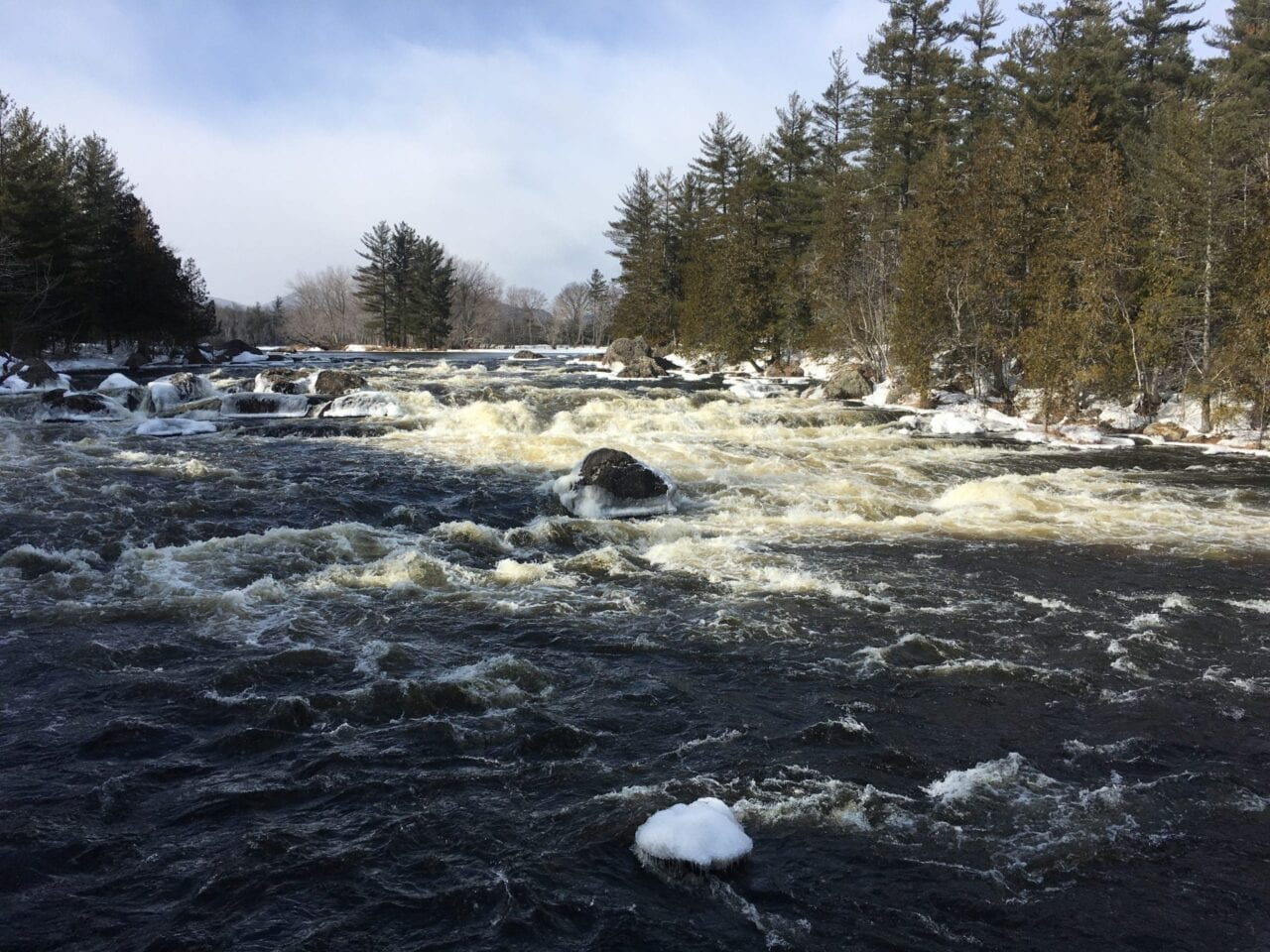 Sunlight illuminates whitewater on a rocky river.